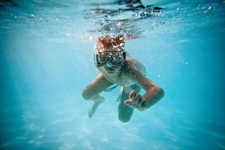 boy under water in pool photo