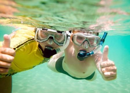 snorkeling: Two children under water in masks