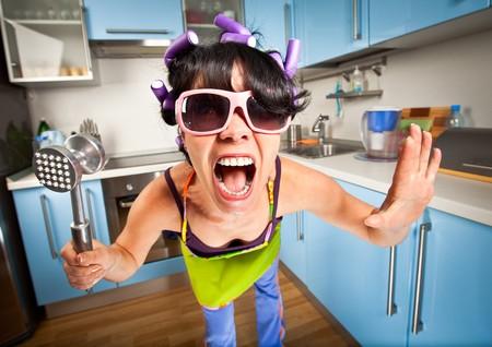 loco: ama de casa loco en un interior de la cocina  Foto de archivo