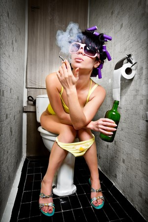 drunk: girl sits in a toilet with an alcohol bottle Stock Photo