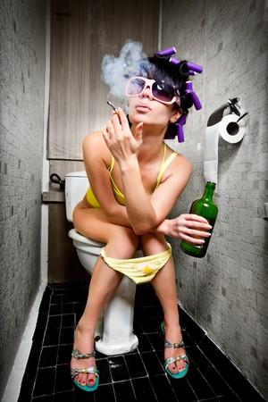 bebidas alcoh�licas: ni�a sentada en un retrete con una botella de alcohol  Foto de archivo