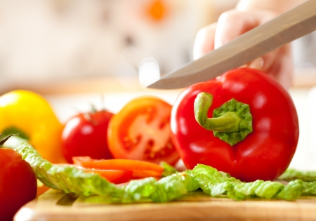 cooking chef: Womans hands cutting tomato bell pepper, behind fresh vegetables. Stock Photo