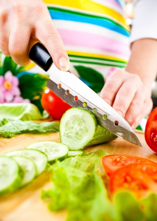 Womans hands cutting cucumber, behind fresh vegetables. photo