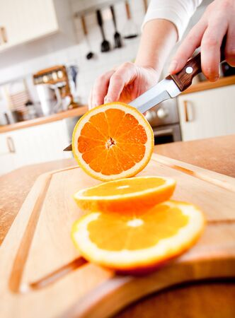 chopping: Womans hands cutting fresh orange on kitchen Stock Photo