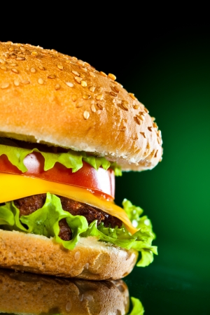 Tasty and appetizing hamburger on a darkly green background photo
