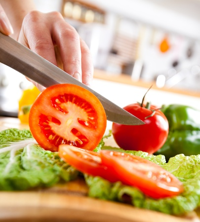 chopping: Womans hands cutting tomato, behind fresh vegetables. Stock Photo