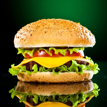 comida rapida: Apetecible y sabrosa hamburguesa sobre un fondo verde oscuro