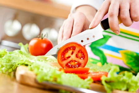 Womans hands cutting tomato, behind fresh vegetables. photo