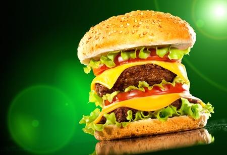 papas fritas: Sabrosa hamburguesa y papas fritas sobre un fondo oscuro
