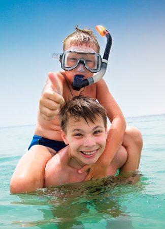 adventure holiday: Two boys in the sea on a beach