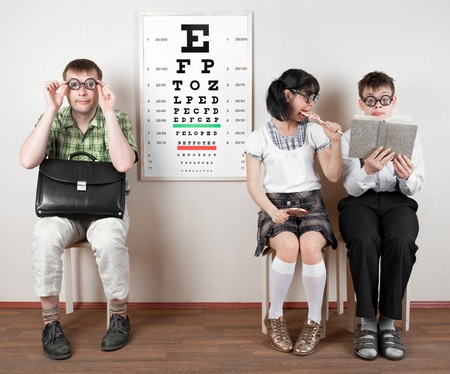 exams: three person wearing spectacles in an office at the doctor Stock Photo