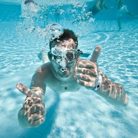 man floats underwater in pool photo