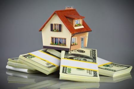 worth: house on packs of banknotes on a grey background