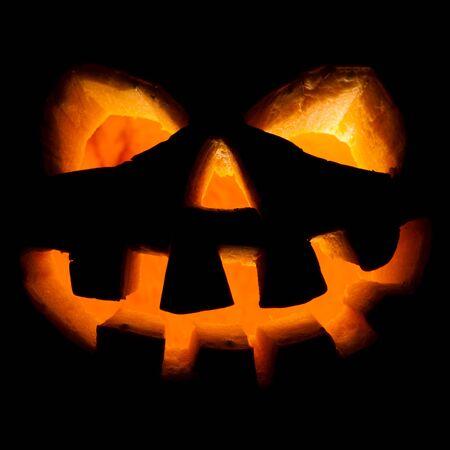 lighting background: Scary old jack-o-lantern on black background.