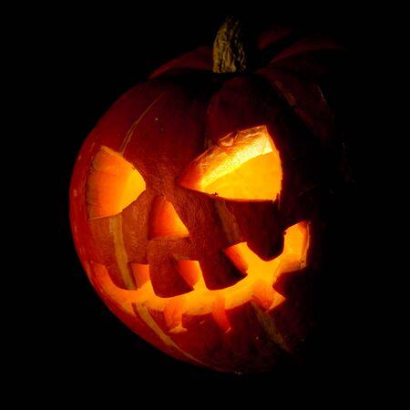 Scary old jack-o-lantern on black background. photo