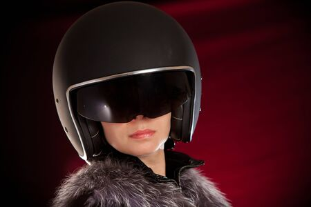 Biker girl in a helmet on a red background photo
