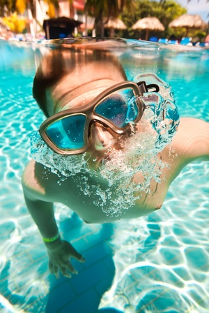 teenager floatsunder water in pool Stock Photo - 11986444