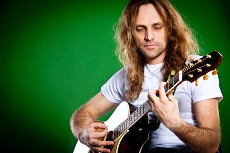 a guitarist boy playing guitar: man with a guitar on a green background