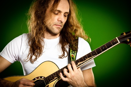 man with a guitar on a green background Stock Photo - 12282458