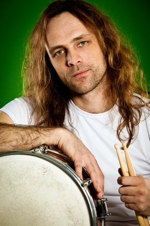 percussionist: Portrait of the drummer man on a green background