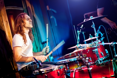 drummer: musician playing drums on a red background Stock Photo