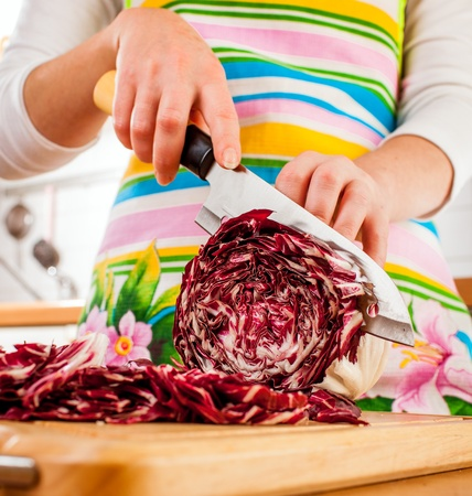 red cabbage: Womans hands cutting red cabbage, behind fresh vegetables. Stock Photo