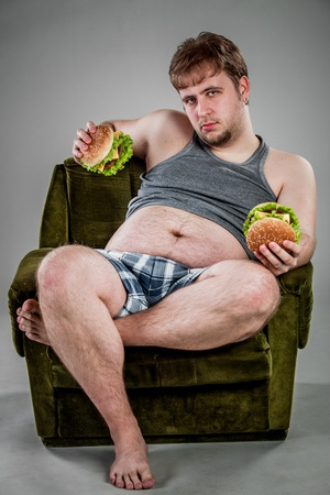 big belly: fat man eating hamburger seated on armchair