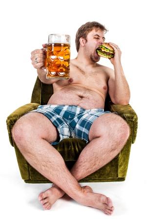 man eten: dikke man het eten van hamburger gezeten op stoel