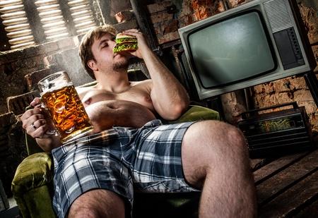 sobre peso: hamburguesa hombre gordo comiendo sentado en el sillón Foto de archivo