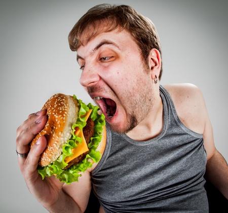 hombre comiendo: hamburguesa hombre gordo comiendo sentado en el sillón Foto de archivo