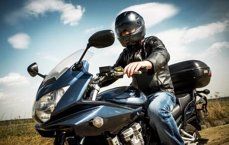 motociclista: El hombre del motorista se sienta en una bicicleta