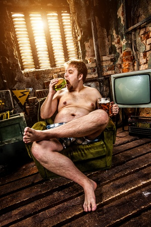 hombre sentado: hamburguesa hombre gordo comiendo sentado en el sill�n Foto de archivo