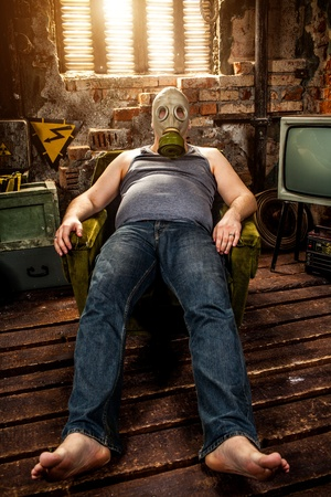 person in a gas mask sits on an armchair photo