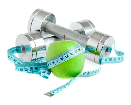 pesas: Pesas con una manzana sobre un fondo blanco. Un estilo de vida saludable