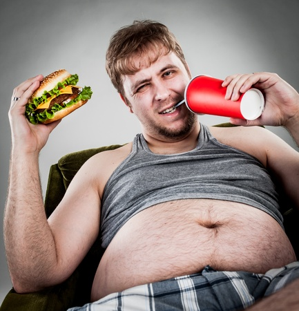 overweight man: fat man eating hamburger seated on armchair