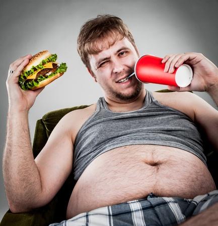 sobre peso: hombre gordo comiendo hamburguesa sentado en la butaca