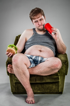 pancia grassa: l'uomo grasso mangia hamburger seduto sulla poltrona Archivio Fotografico