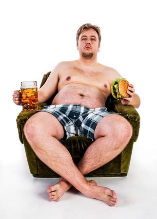 fat man: fat man eating hamburger seated on armchair