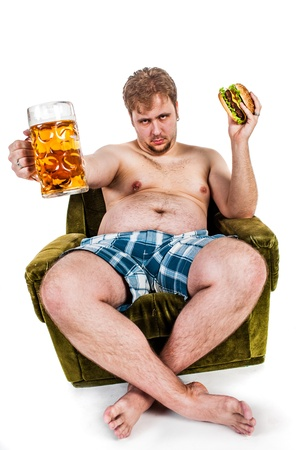 upset stomach: fat man eating hamburger seated on armchair