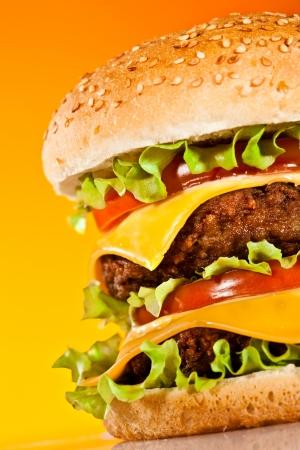 HAMBURGESA: Hamburguesa sabrosa y apetitosa en un fondo amarillo
