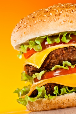 Tasty and appetizing hamburger on a yellow background photo