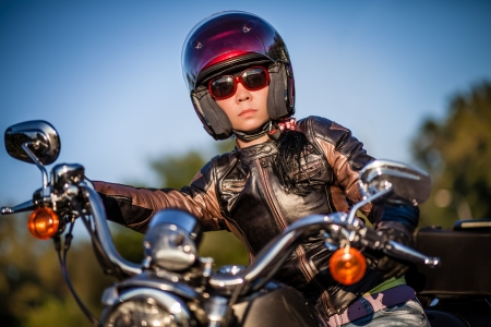 Biker girl sits on a motorcycle photo