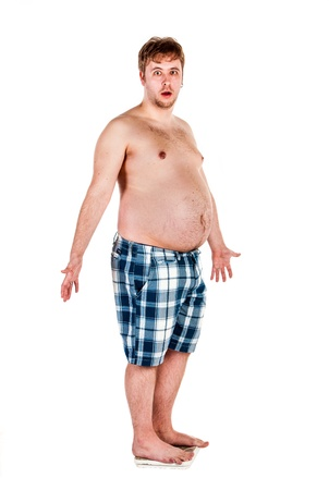 sobre peso: El sobrepeso, hombre gordo se pesa en escalas. Foto de archivo