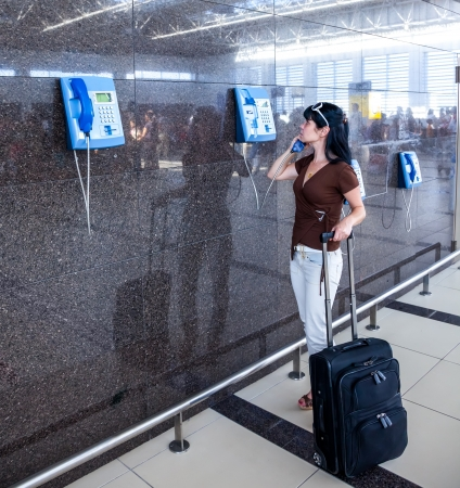 tardiness: Woman calling on the phone at the airport