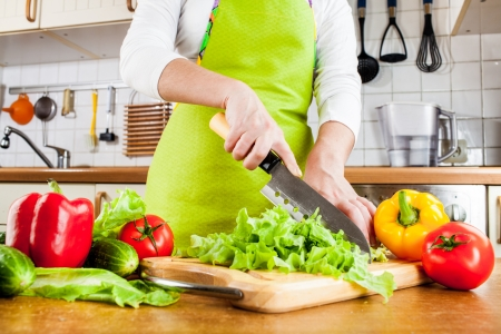 knife tomato: Womans hands cutting lettuce, behind fresh vegetables.