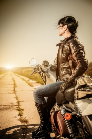 woman motorcycle: Biker girl sits on a motorcycle