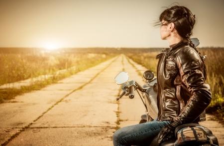 motorcycle road: Biker girl sits on a motorcycle