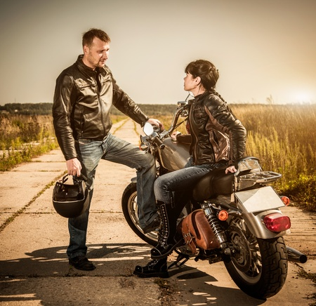 motorcyclist: Biker man and girl sits on a bike