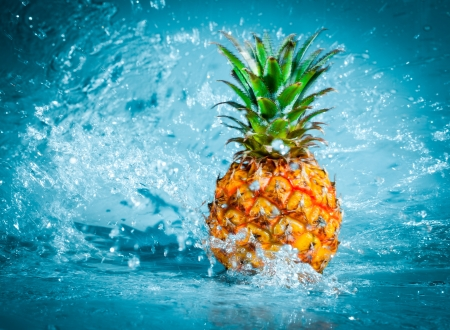 and pineapple juice: Fresh pineapple in water splashes Stock Photo