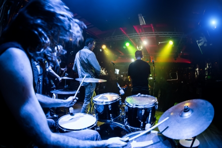 rock guitarist: Performances of the musicians, the drummer in the foreground